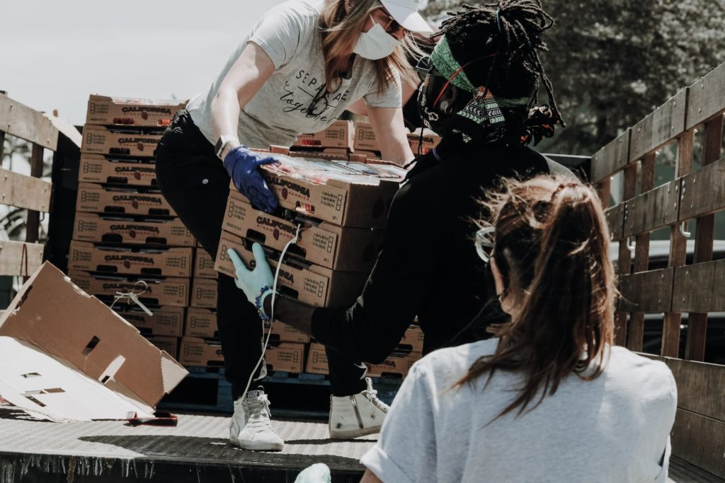 People helping each other lifting boxes