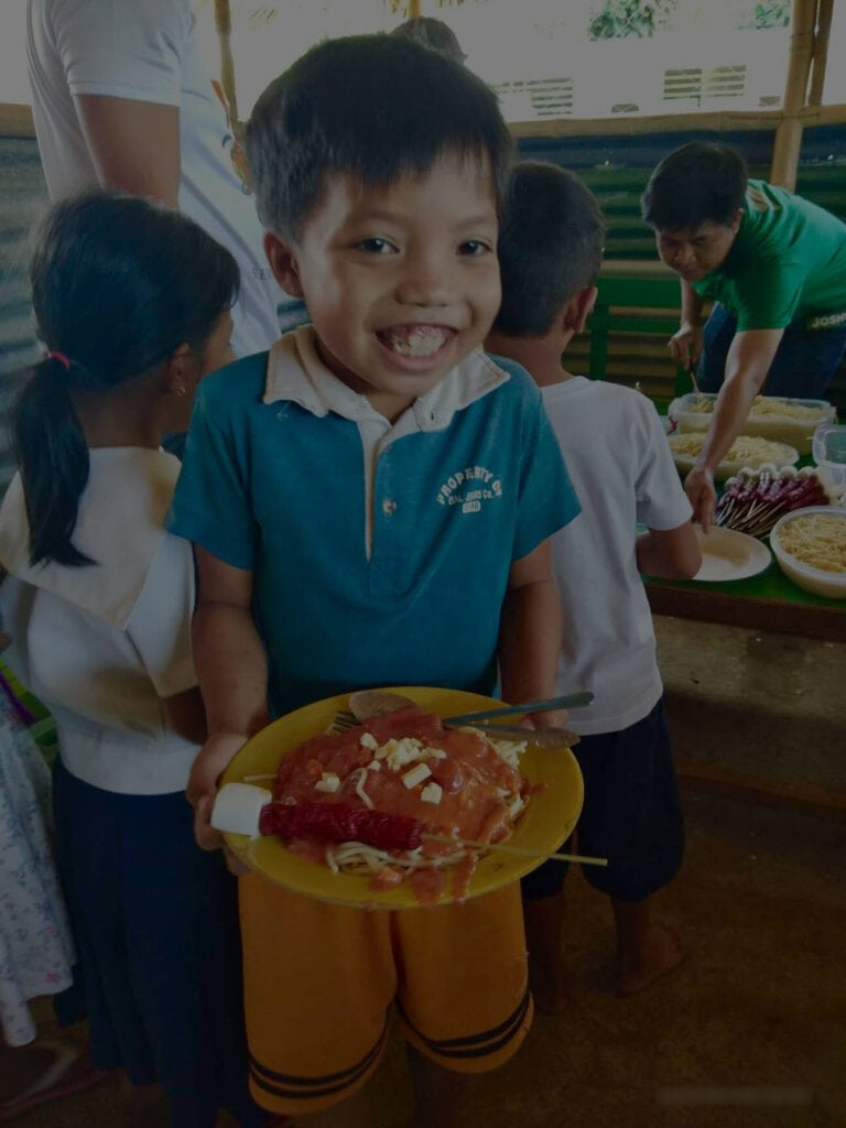 A little boy holding a plate with foods